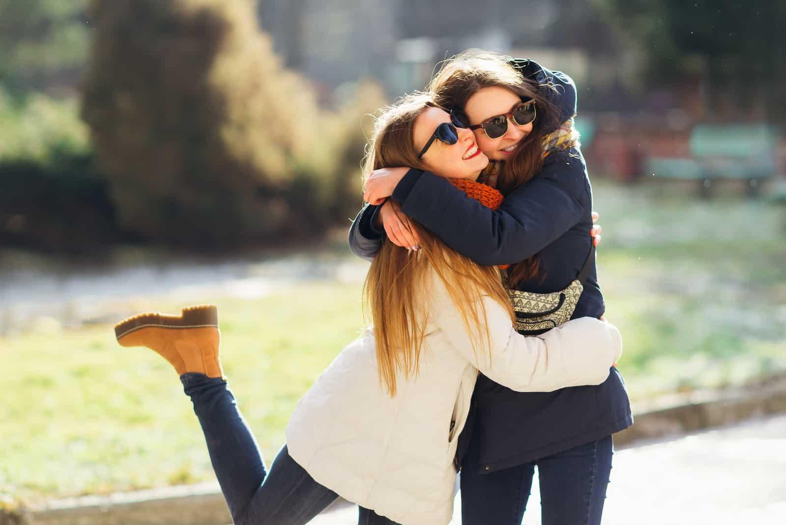 Ung flicka som kramar hennes äldre syster som ler