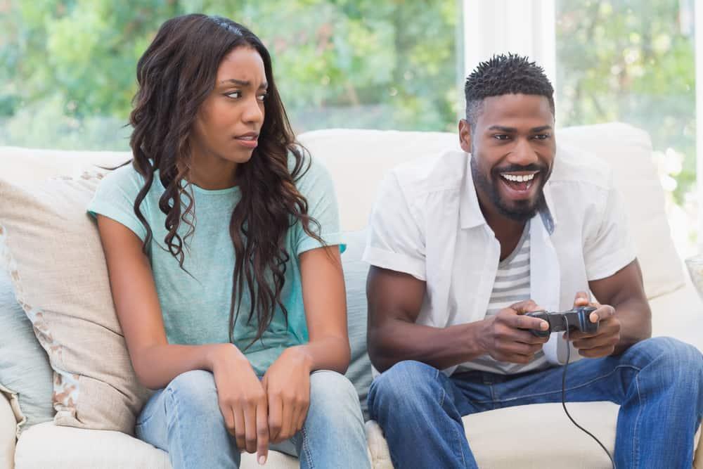 Upprörd kvinna som ignoreras av sin partner hemma i vardagsrummet