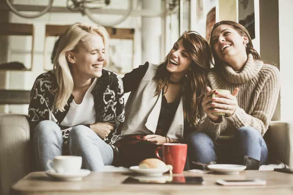 tre kvinnor sitter och skrattar