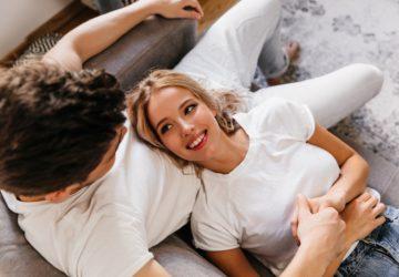 en attraktiv leende blondin ligger i pojkvänens knä