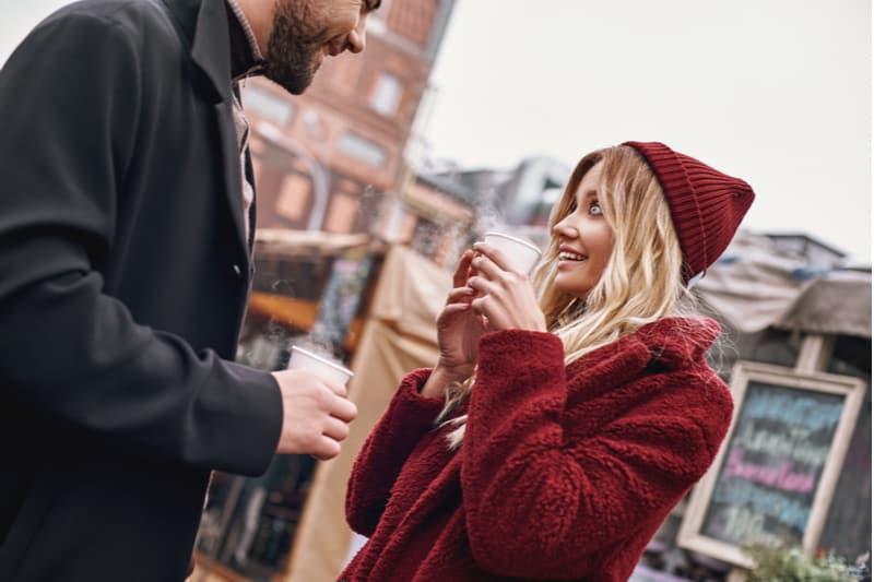älskande par som står utanför och dricker kaffe och pratar