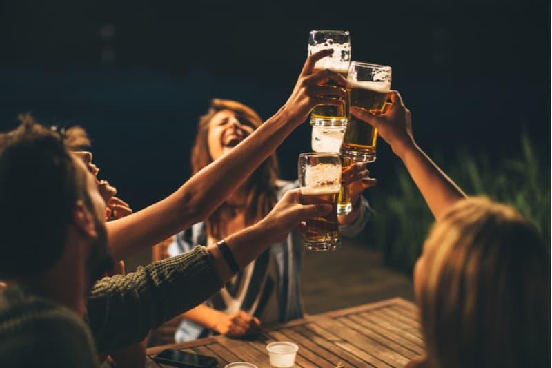 en grupp vänner sitter ute vid ett bord på kvällen och dricker öl