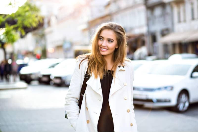 en kvinna med långt brunt hår står på gatan och ler