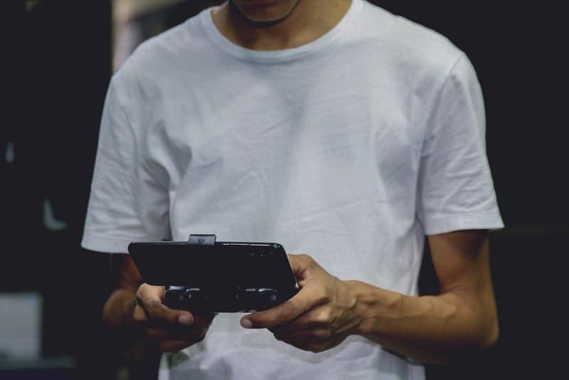 en man i en vit T-shirt som spelar ett spel på sin smartphone