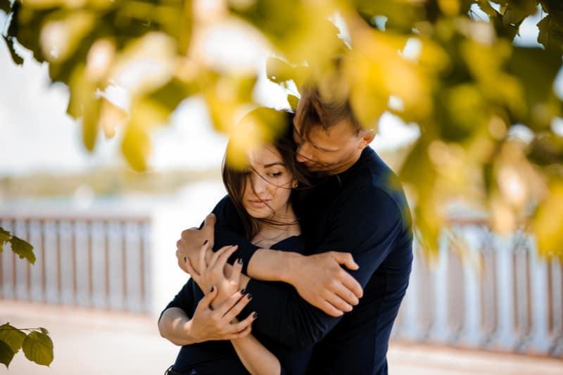 en man kramar en sorglig kvinna bakifrån