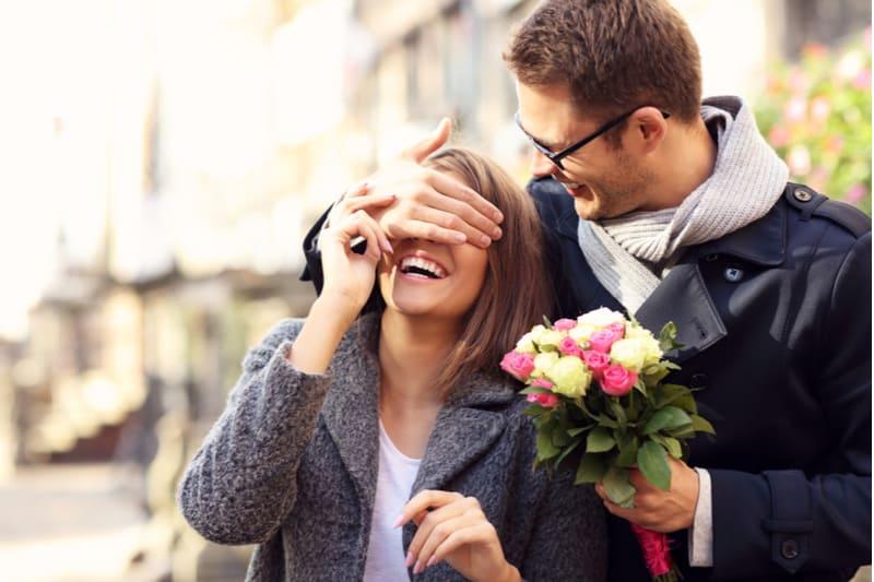 en man med glasögon ger en bukett blommor till sin flickvän