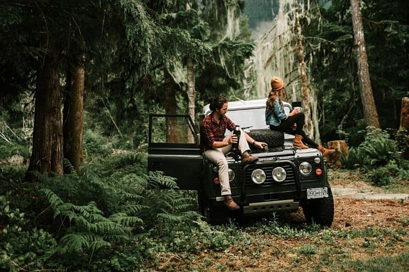 ett kärleksfullt par som sitter på huven på en jeep i skogen och dricker kaffe