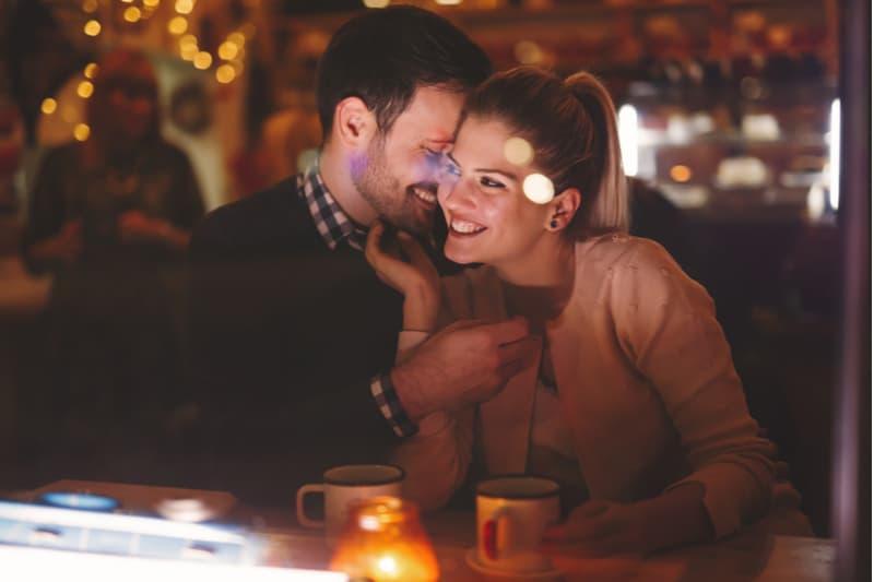 ett leende älskande par som kramar på ett kafé