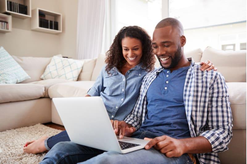 ett leende svart par använder en bärbar dator