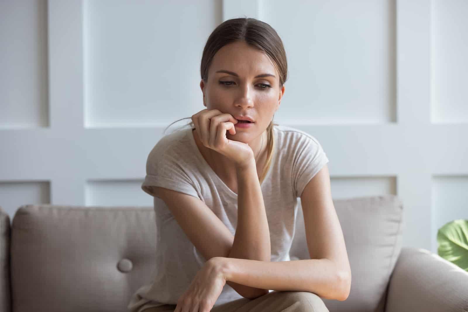 fundersam kvinna som sitter på soffan