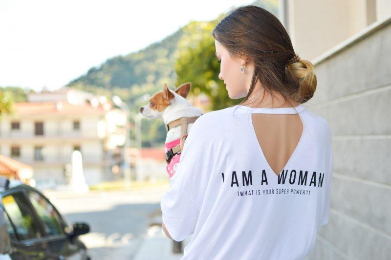 kvinna som bär den vita skjortainnehavhunden i händer