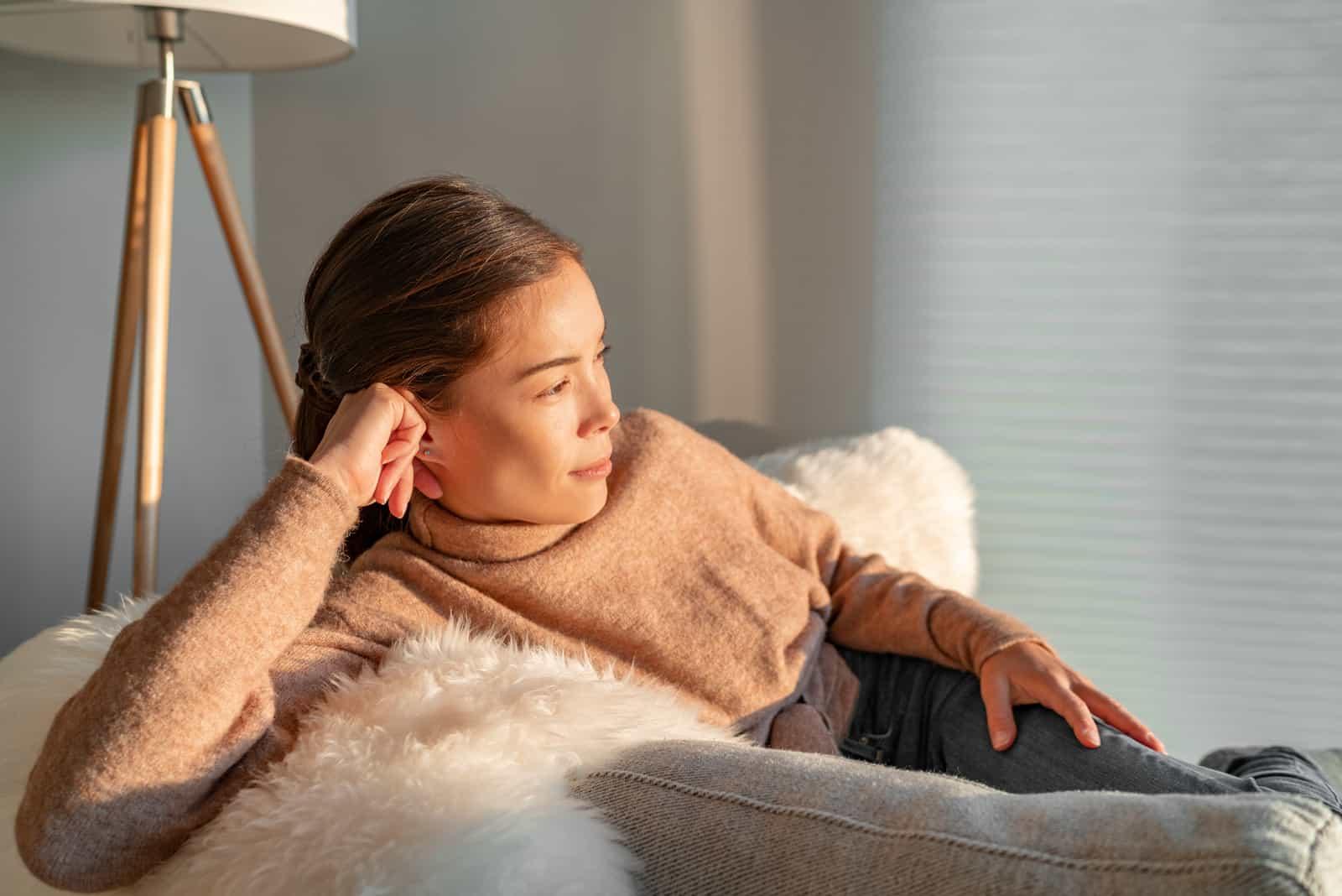 kvinna som sitter på soffan och tänker