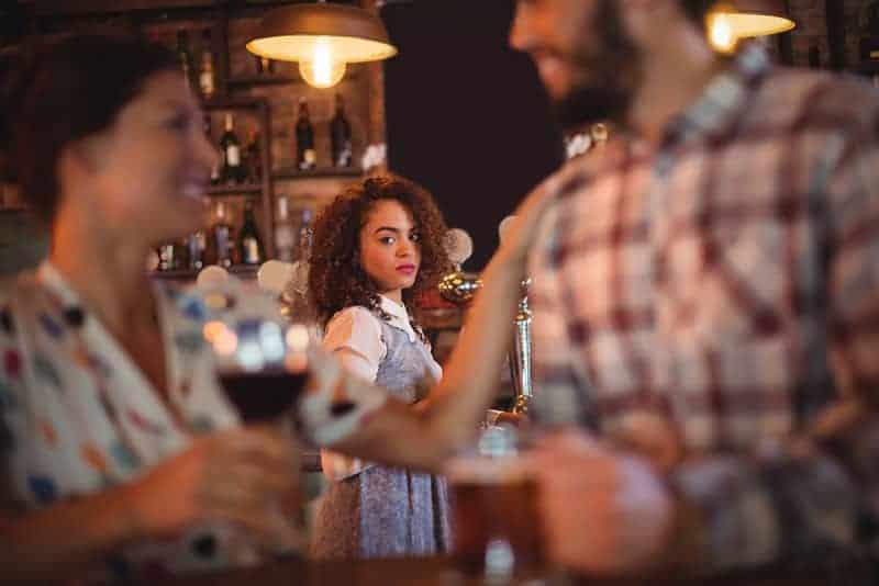 kvinna som tittar på par i baren
