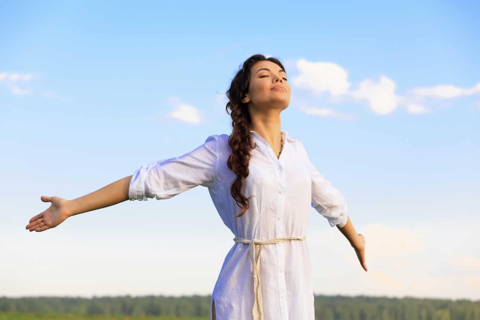 kvinnan står med utsträckta armar