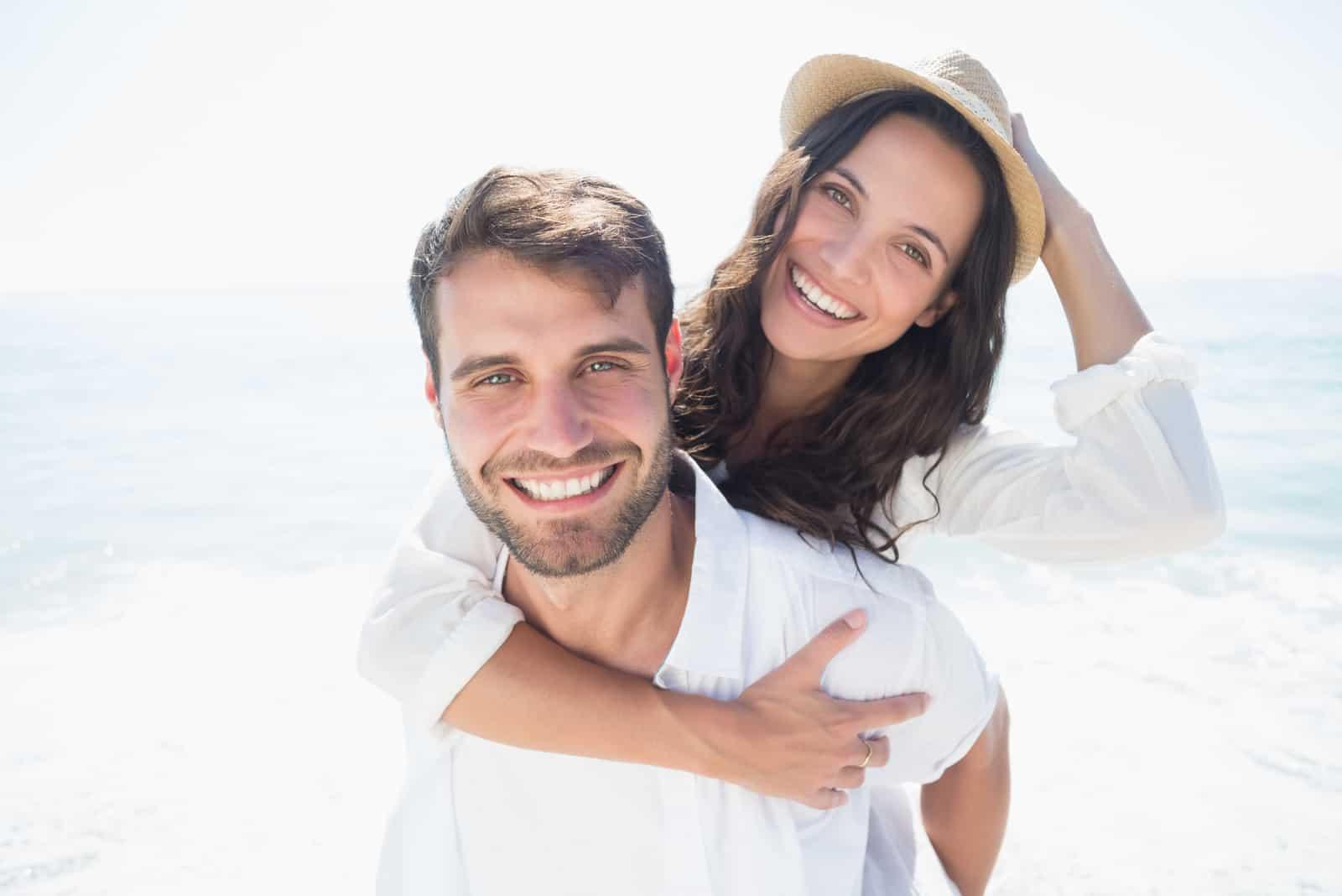 lyckliga par som ler på stranden
