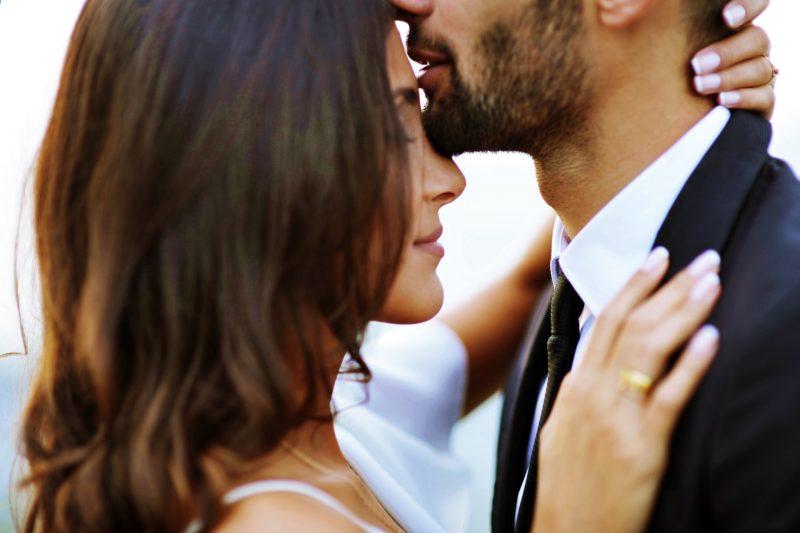 man kysser kvinna i pannan