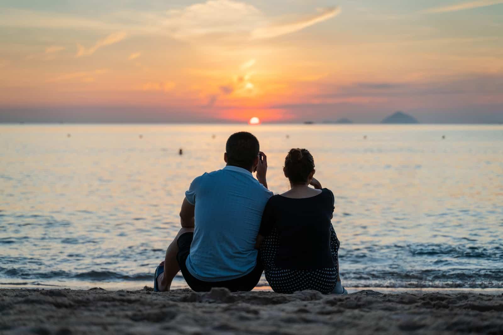 man och kvinna sitter på stranden