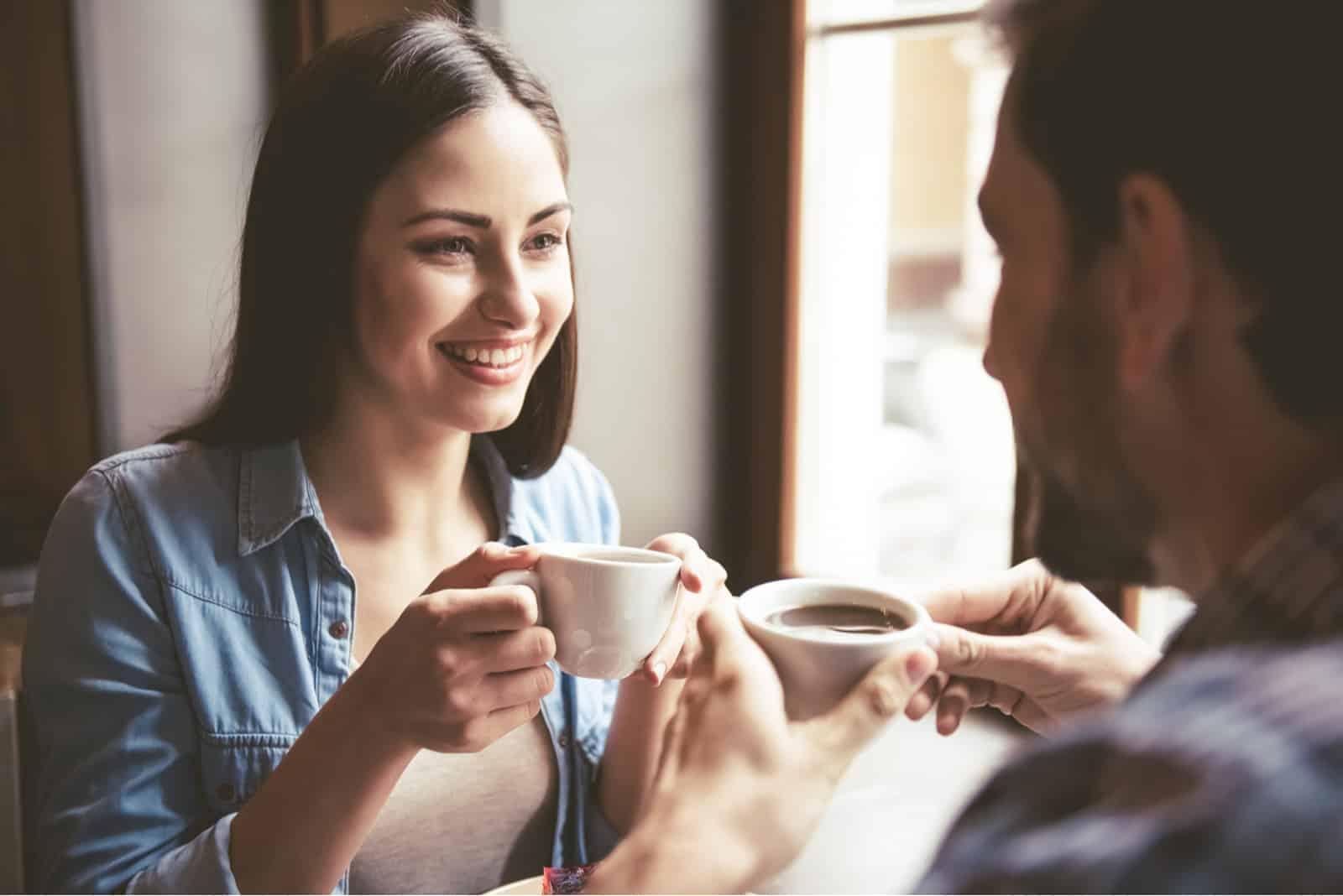 par sitter och dricker kaffe
