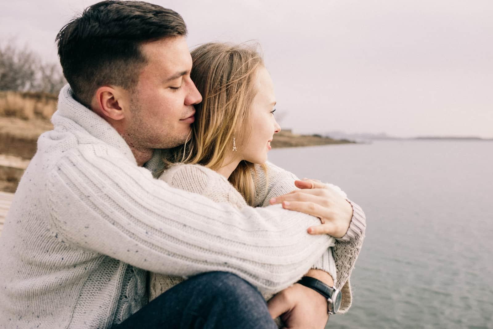 par sitter vid sjön kramar