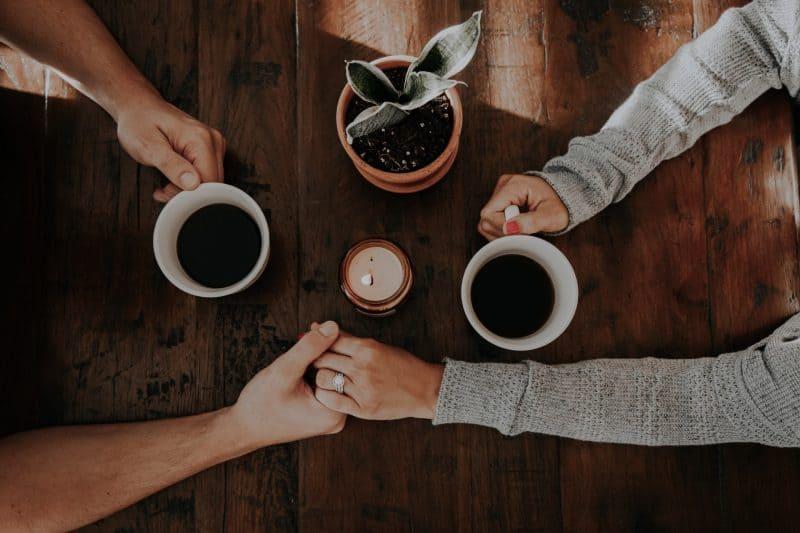 par som dricker kaffe som håller hand
