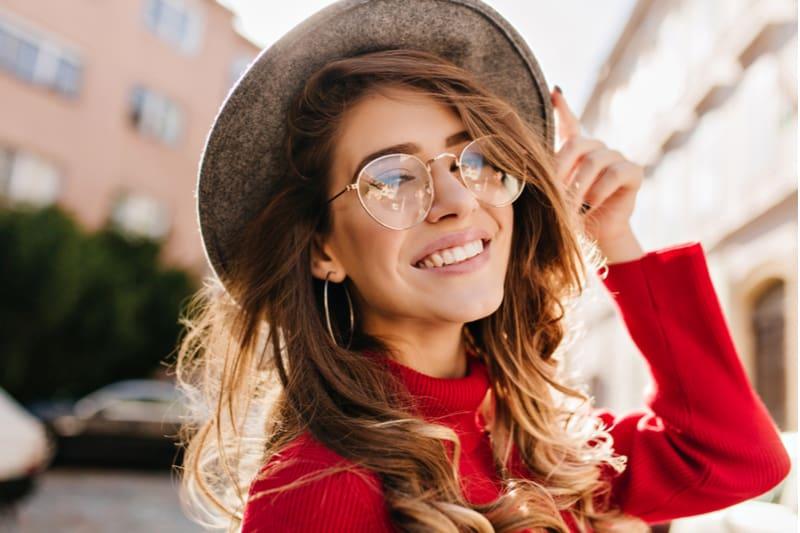 porträtt av en vacker leende brunett med glasögon