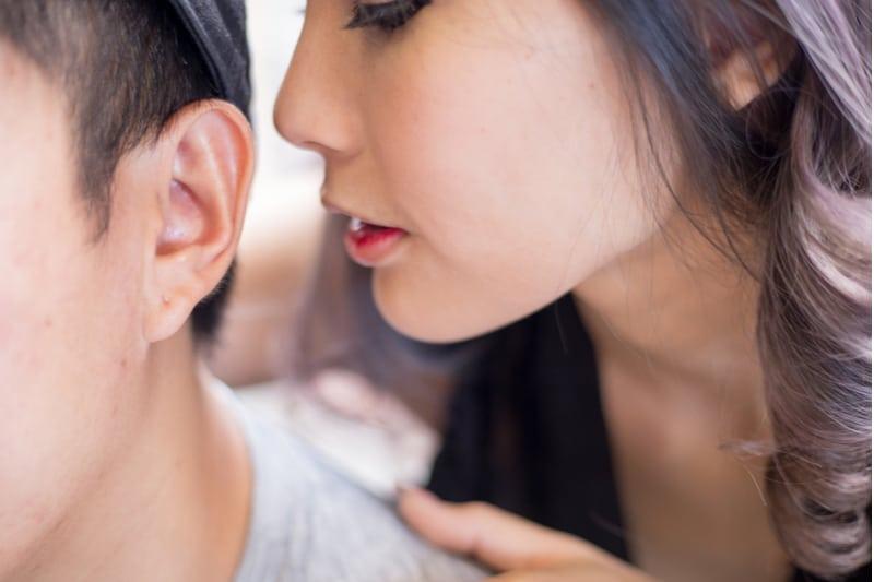 sexig kvinna viskar något i en mans öra