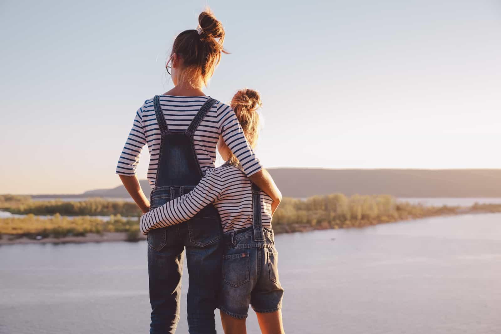 systrar som kramar medan de tittar på naturen