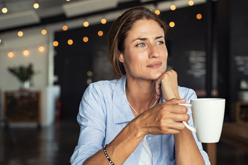 tankeväckande kvinna på café
