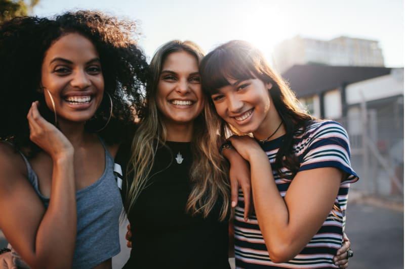 tre unge kvinder smilende