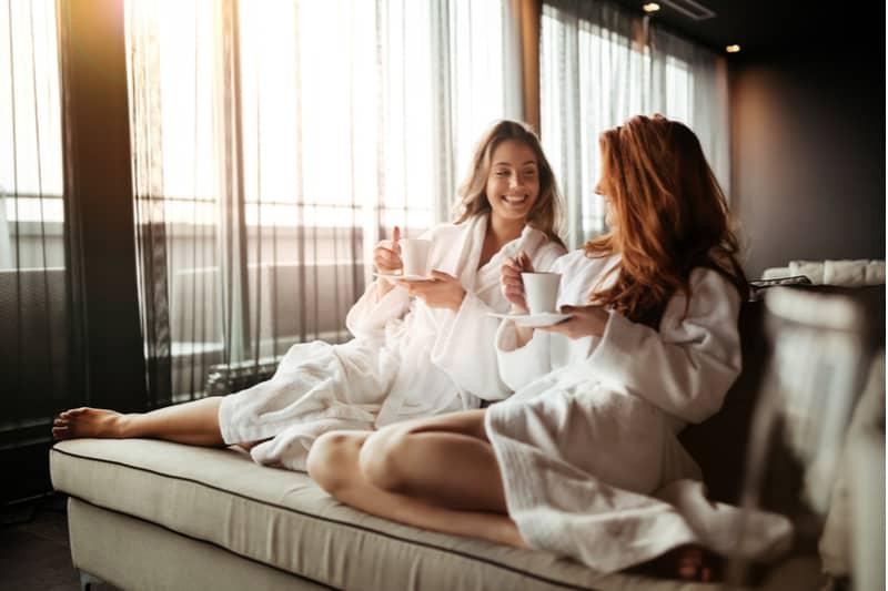 to kvinder sidder på sengen og drikker kaffe