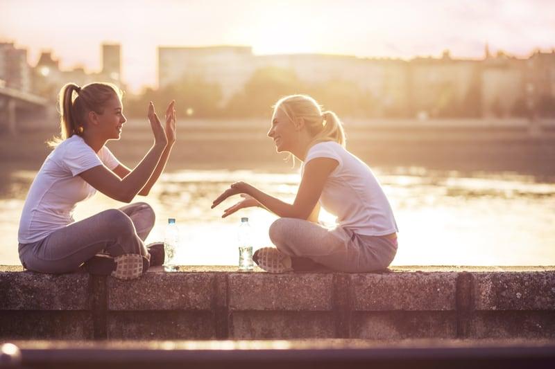 to unge kvinder sidder udendørs