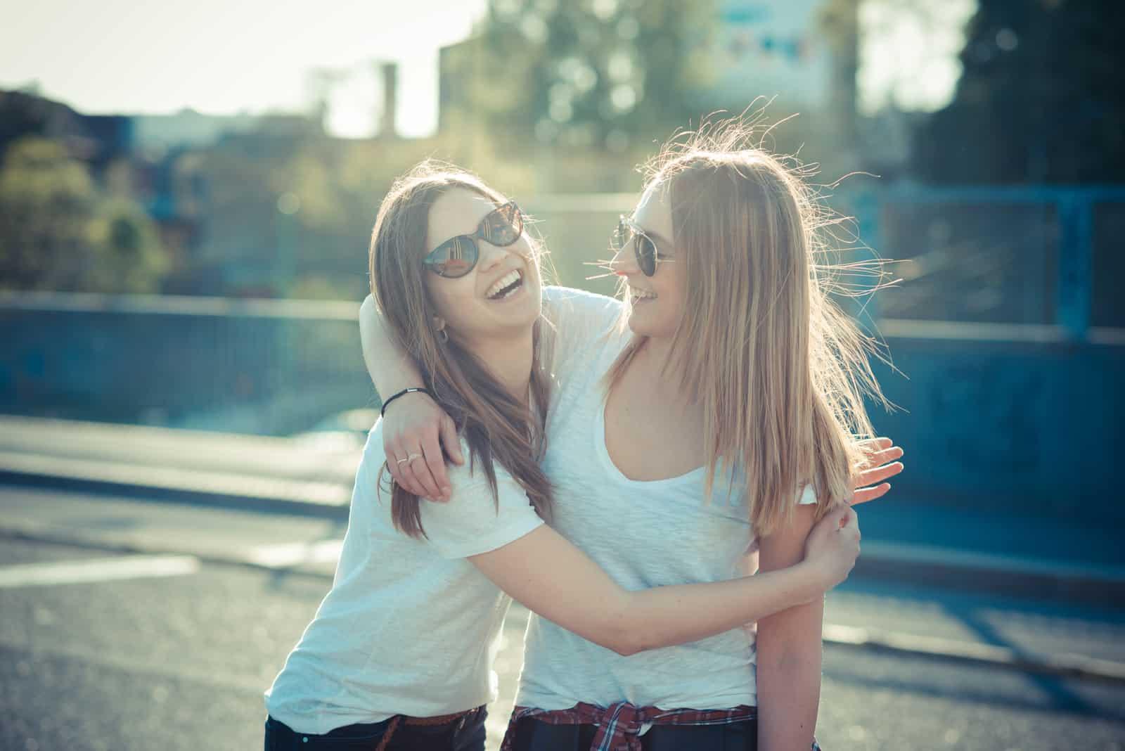 två vackra unga kvinnor som har kul i staden