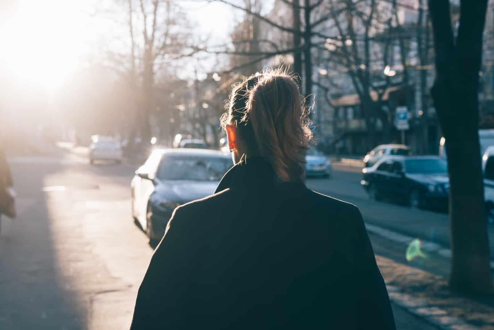ung kvinna som bär svart kappa som går nerför gatan