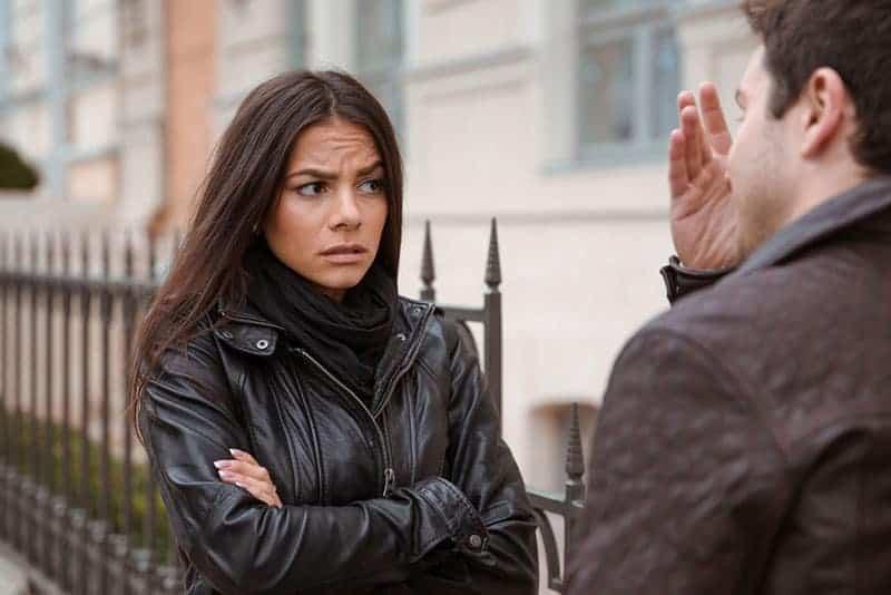 upprörd kvinna med korsade armar som står med mannen utanför