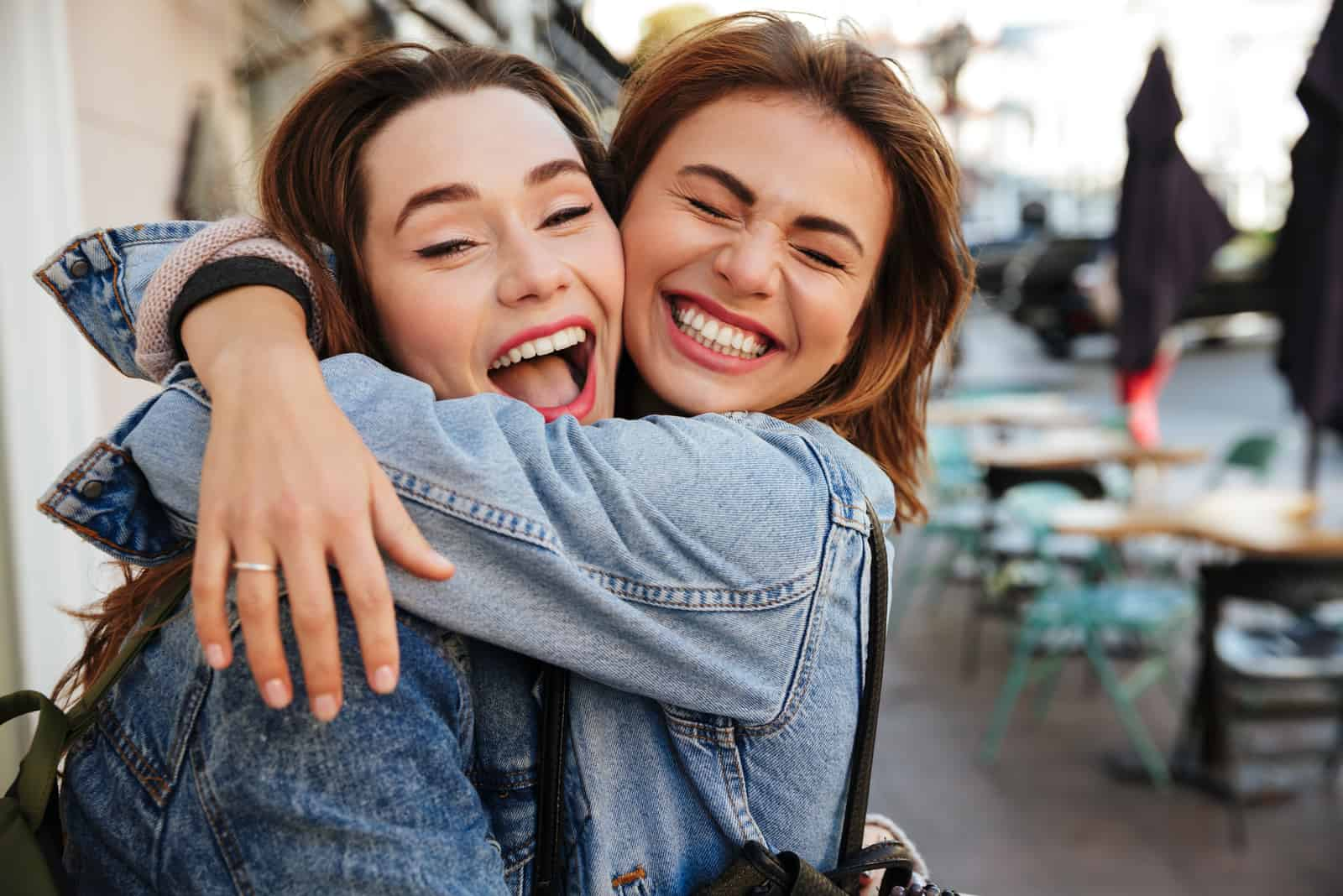 vänner kramar varandra på stadsgatan