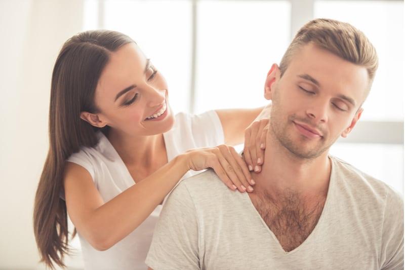 vacker brunett masserar sin pojkvän