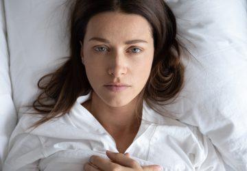 ledsen ung kvinna som ligger i sängen