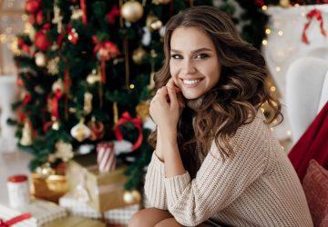 Dana den unga härliga kvinnan i stickad klänning nära julträdet