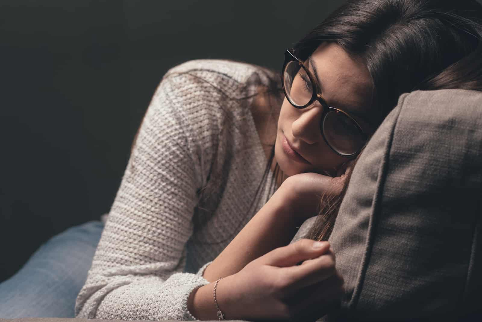 ung kvinna med glasögon som sitter i soffan hemma