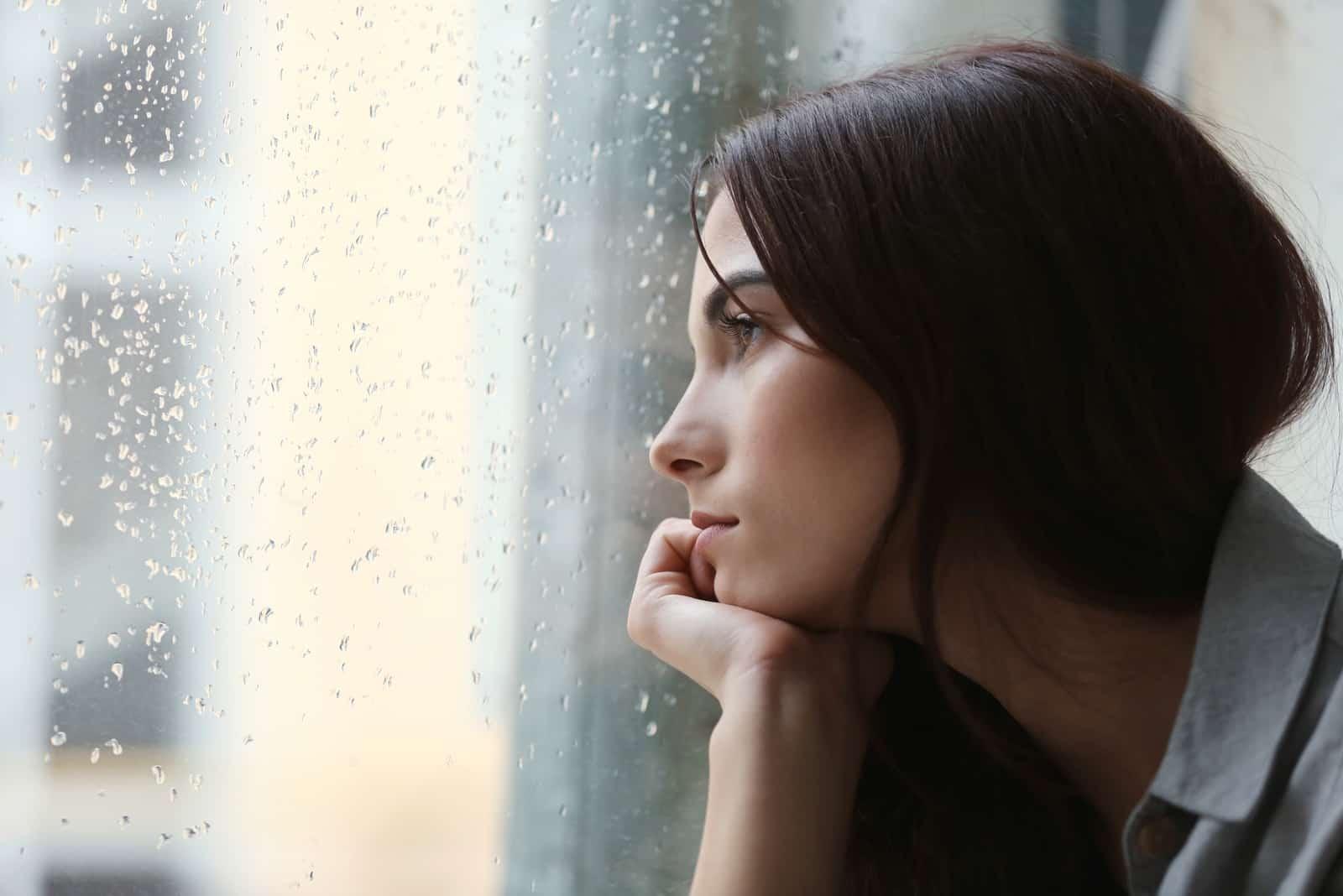 Deprimerad ung kvinna nära fönster hemma