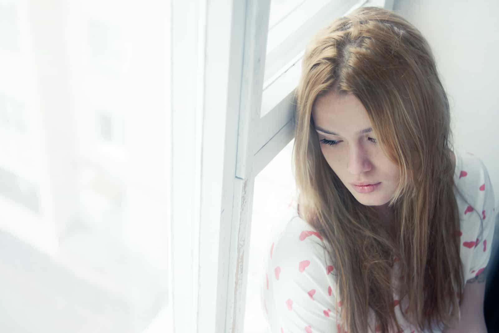 ledsen kvinna som lutar sig mot fönstret