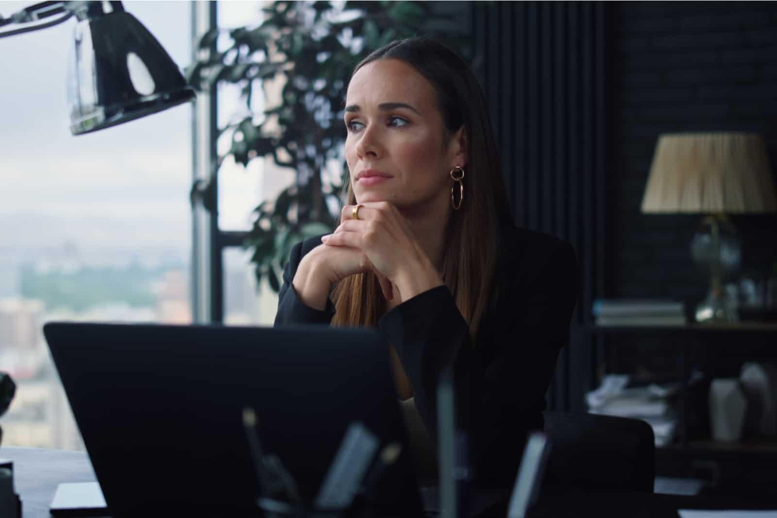Eftertänksam kvinna som i regeringsställning tänker på tabellen
