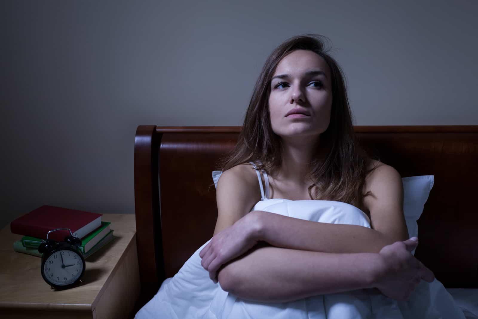 Eftertänksam kvinna som sömnar sömnlös i säng på natten