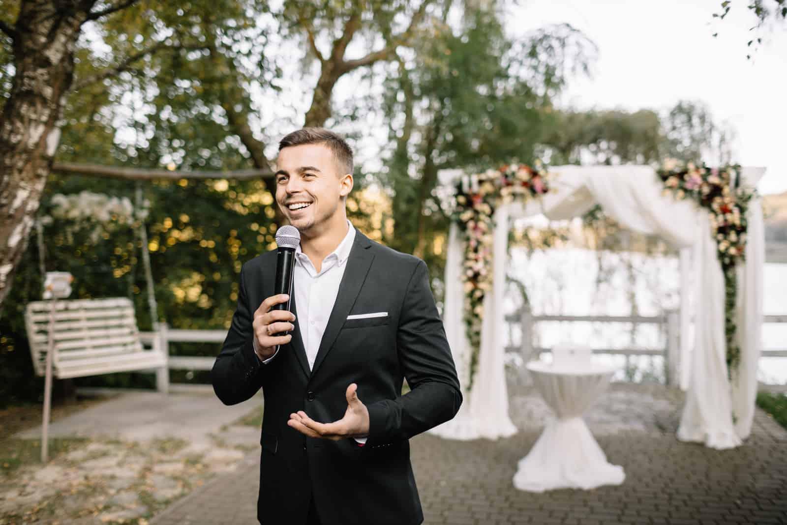 Elegant man med ett tal för mikrofon
