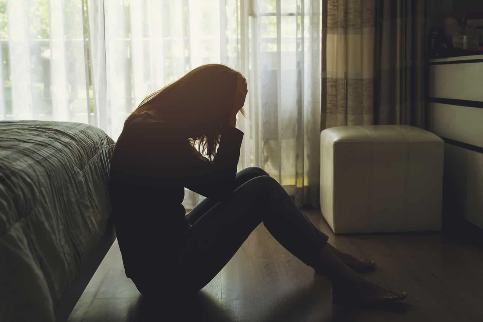 Ensam ung kvinna som känner sig deprimerad och stressad sittande