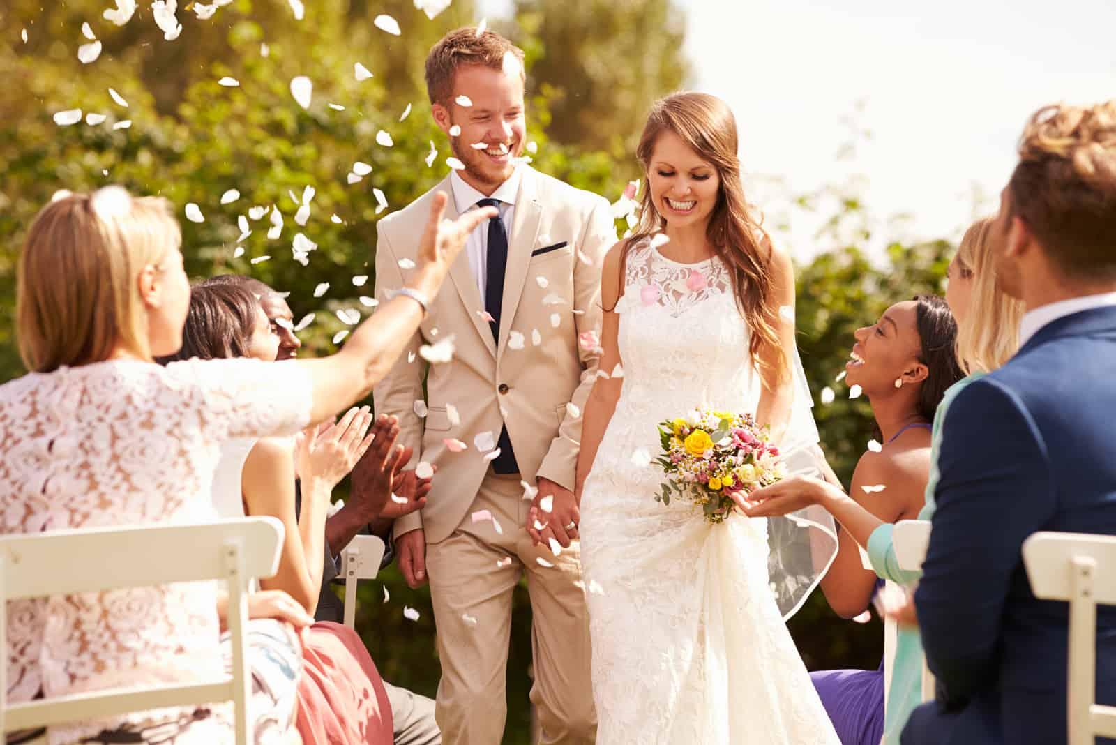 Gäster som kastar konfetti över bruden och brudgummen på bröllopet