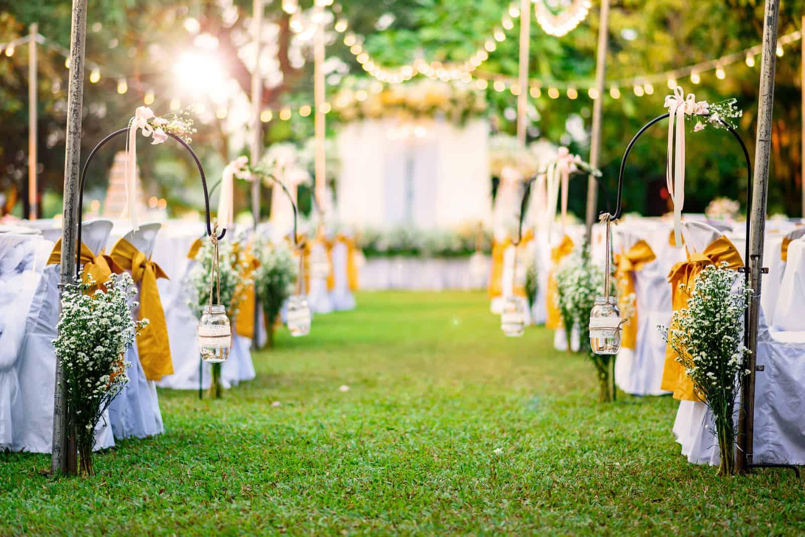 Härlig bröllopceremonihändelse i trädgård vid solnedgången