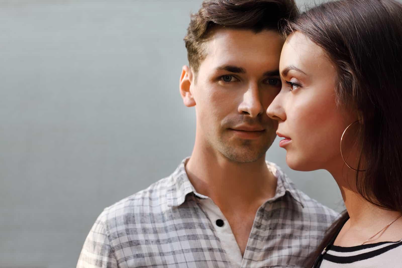 Härlig eftertänksam man och kvinna som står nära den gråa väggen