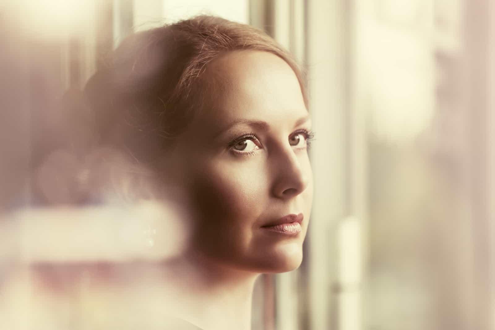 Ledsen härlig kvinna som ser ut fönstret