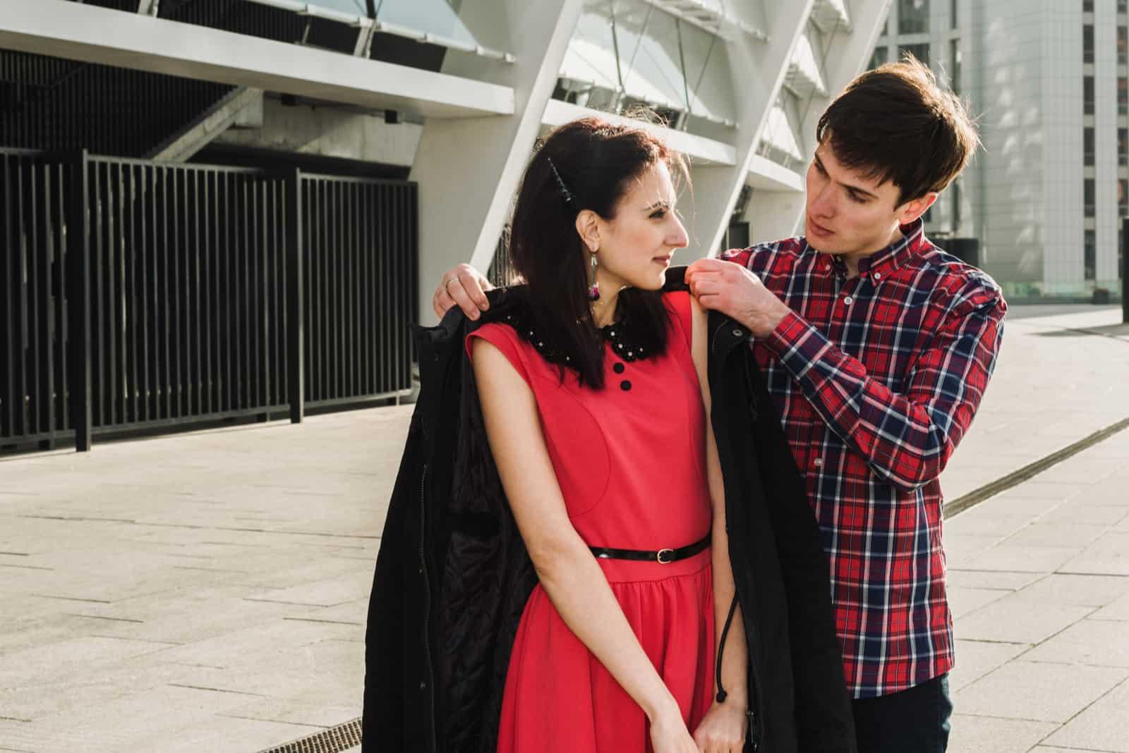 Man som ger kvinnan sin jacka till sin flickvän